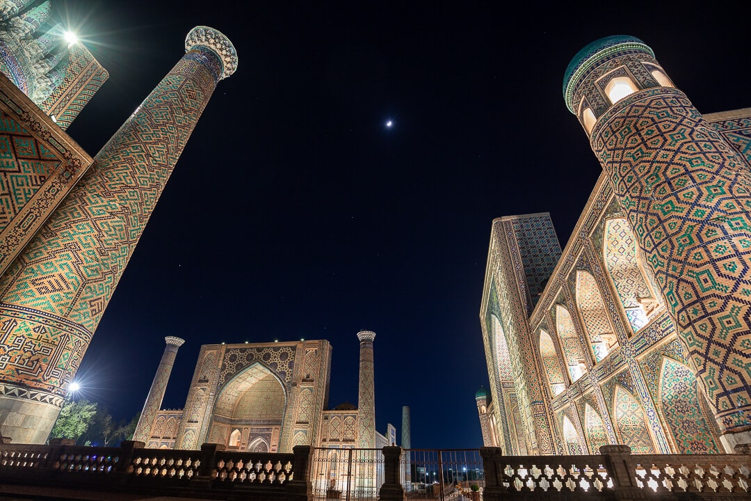 The Registan at night, all three madrassas are lit up and the moon is shining in the middle