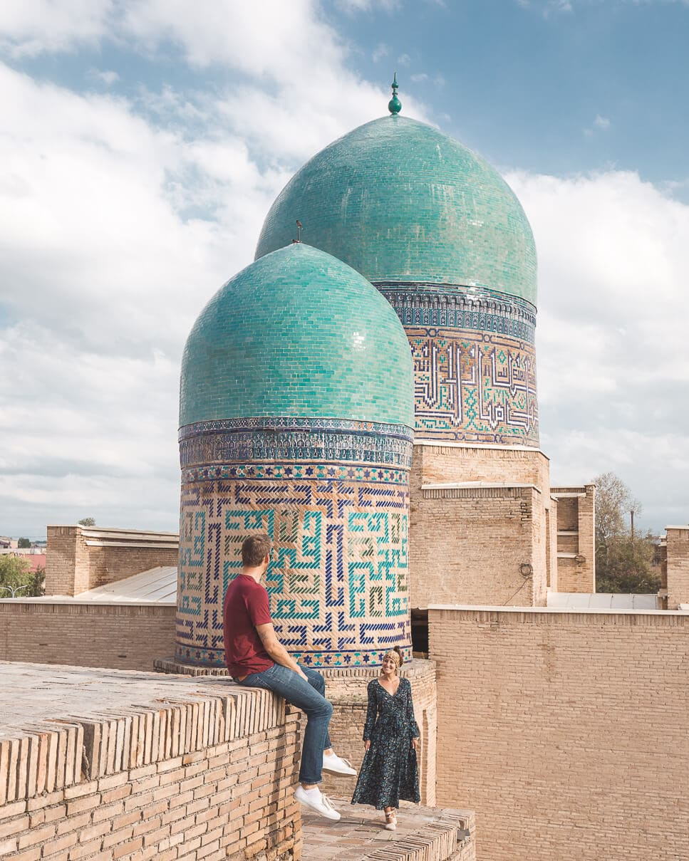 Matt and Sindhya at Shah-i-Zinda mausoleum with two turquoise domes behind them