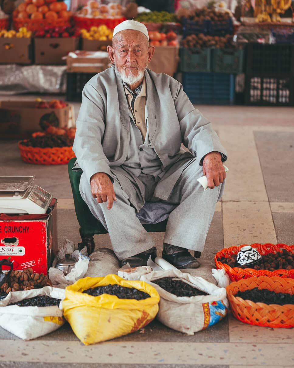 A local Uzbek man sells dried apricots and figs at Siyab Bazaar in Samarkand