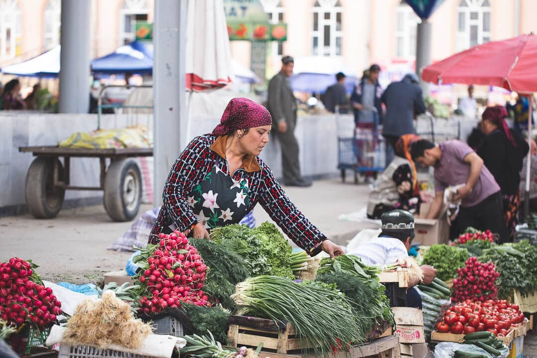 A local Uzbek woman selling vegetables at the Siyab Bazaar. Travel guide to Samarkand.