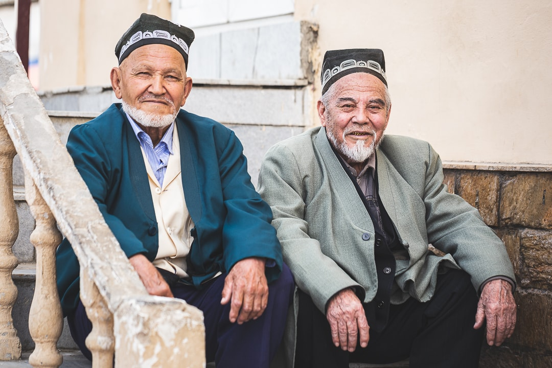 Two Muslim men in Samarkand, Uzbekistan wearing traditional Uzbek skullcaps.