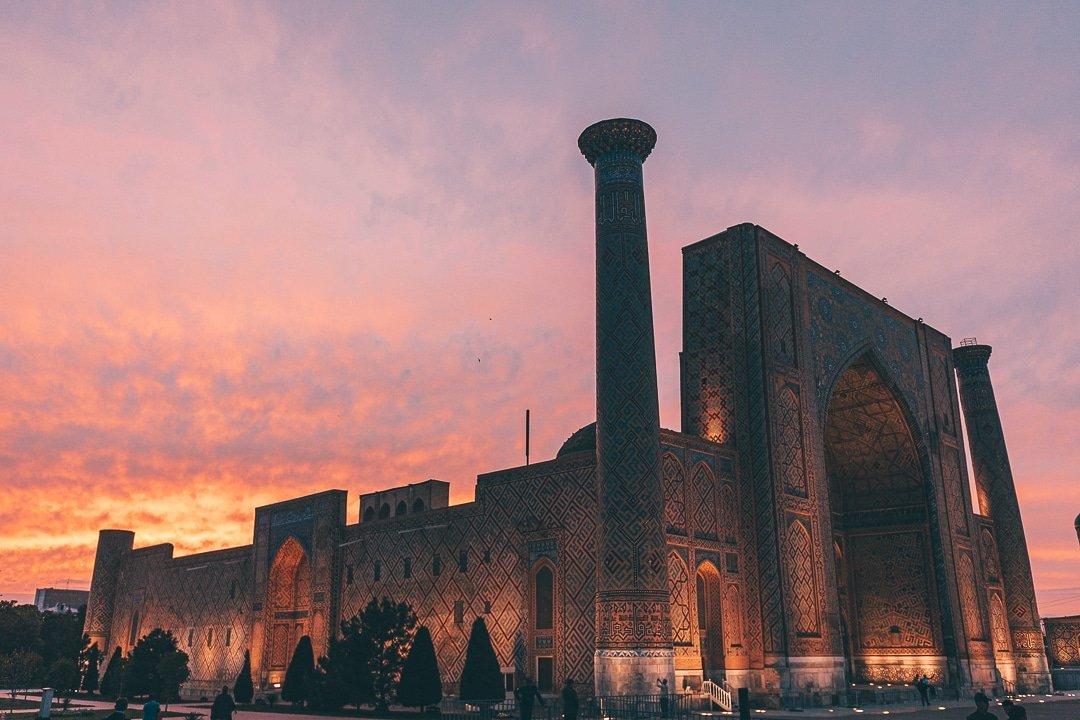 Ulugbek Madrassa lights up at sunset in Samarkand