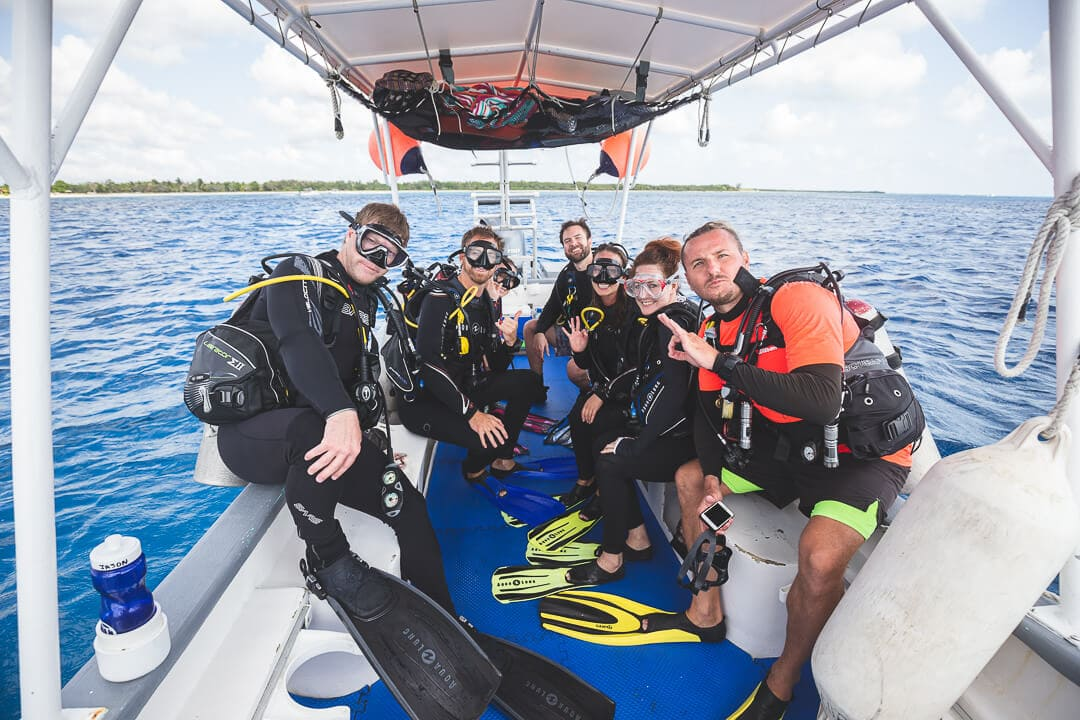 Group of scuba divers posing for a photo on a dive boat. Scuba Tony