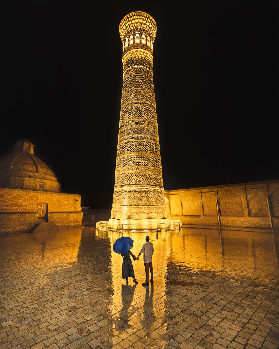 Kalyan minaret lit up at night while Matt and Sindhya stand in front with umbrella in Bukhara